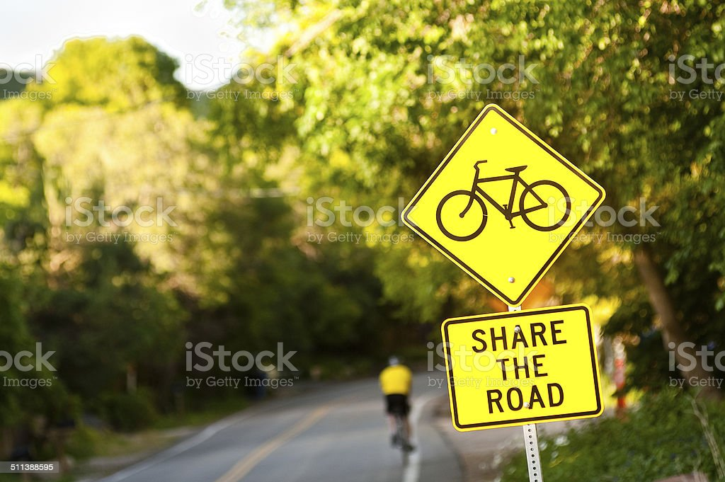Share The Road street sign with a biker. stock photo