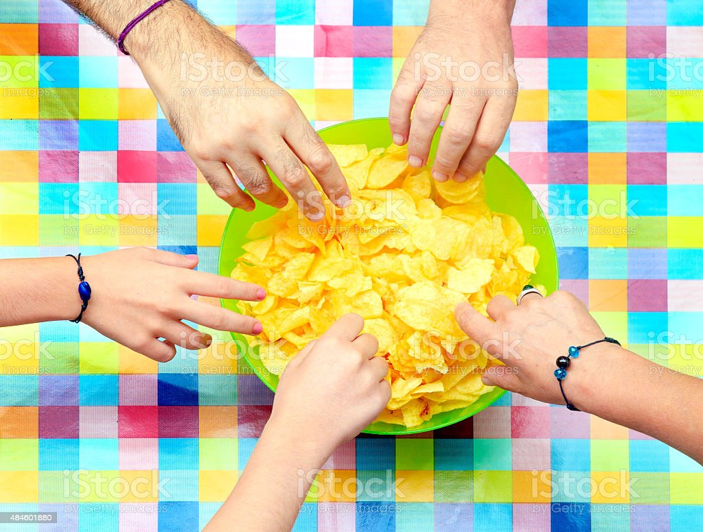 Sharing a bowl of potato chips stock photo