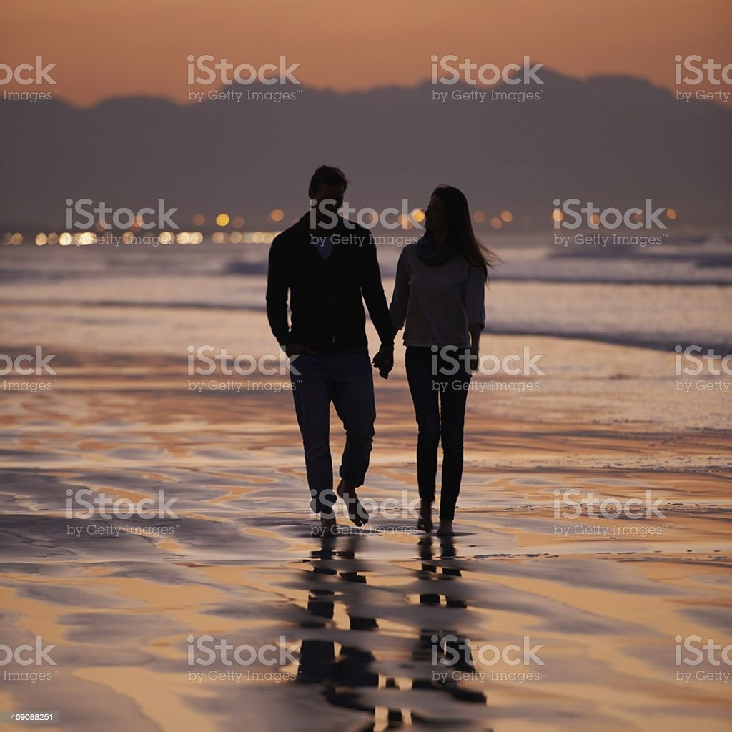Sharing a romantic walk on the beach stock photo