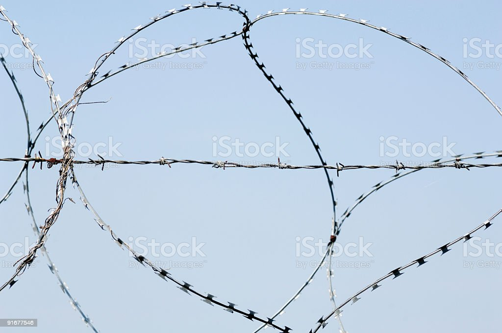 Sharp barbwire fencing against clear sky stock photo