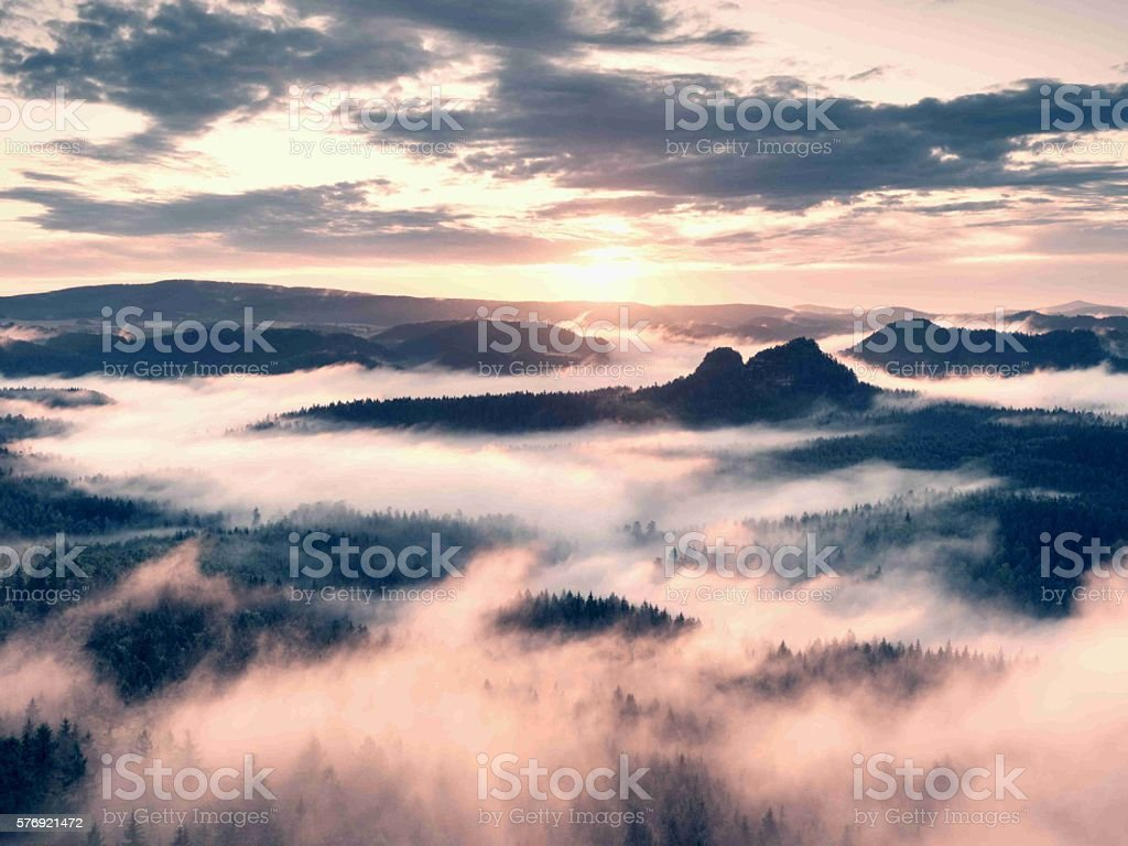 Sharp peaks increased from pink fog in long valley stock photo