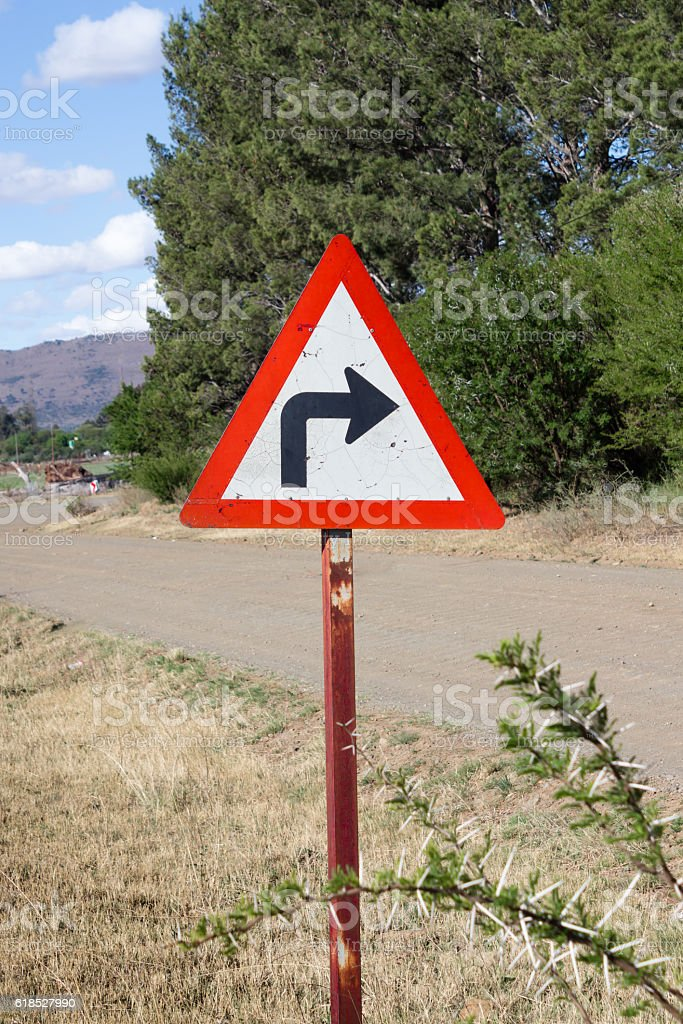 Sharp right hand turn sign next to rural road stock photo