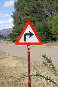 Sharp right hand turn sign next to rural road