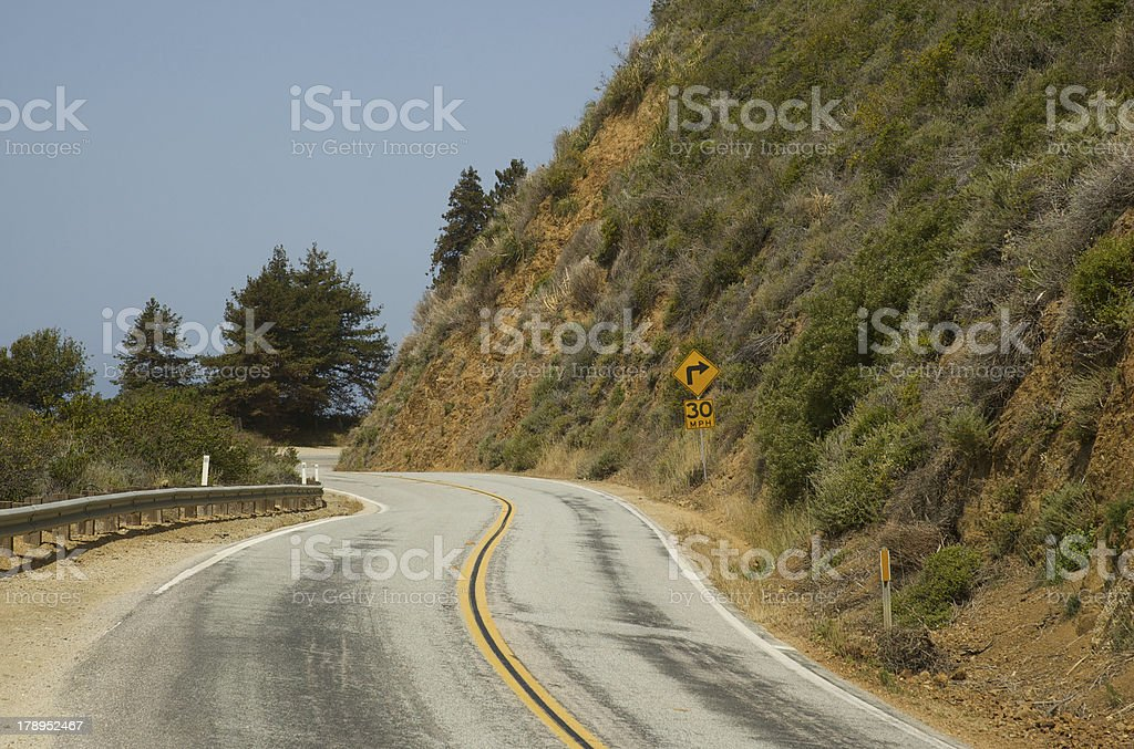 Sharp right turn on a sunny rural highway royalty-free stock photo