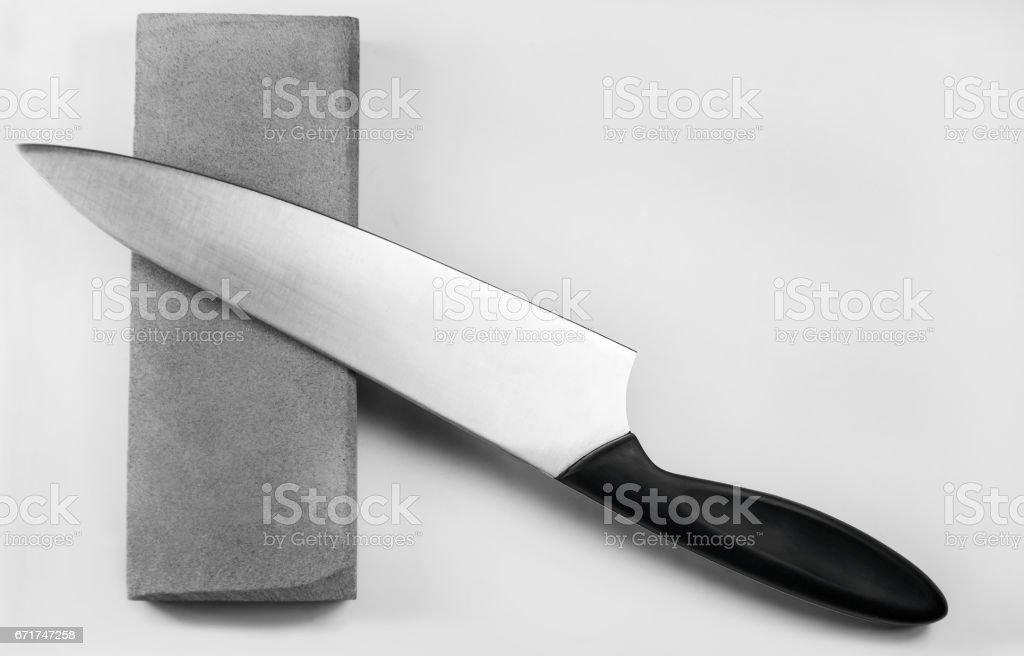 Sharpening a knife on a whetstone, isolated on white background stock photo