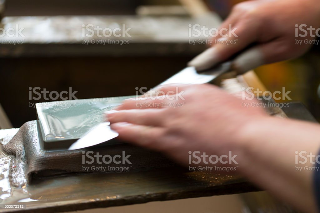 Sharpening Knife on Whetstone stock photo