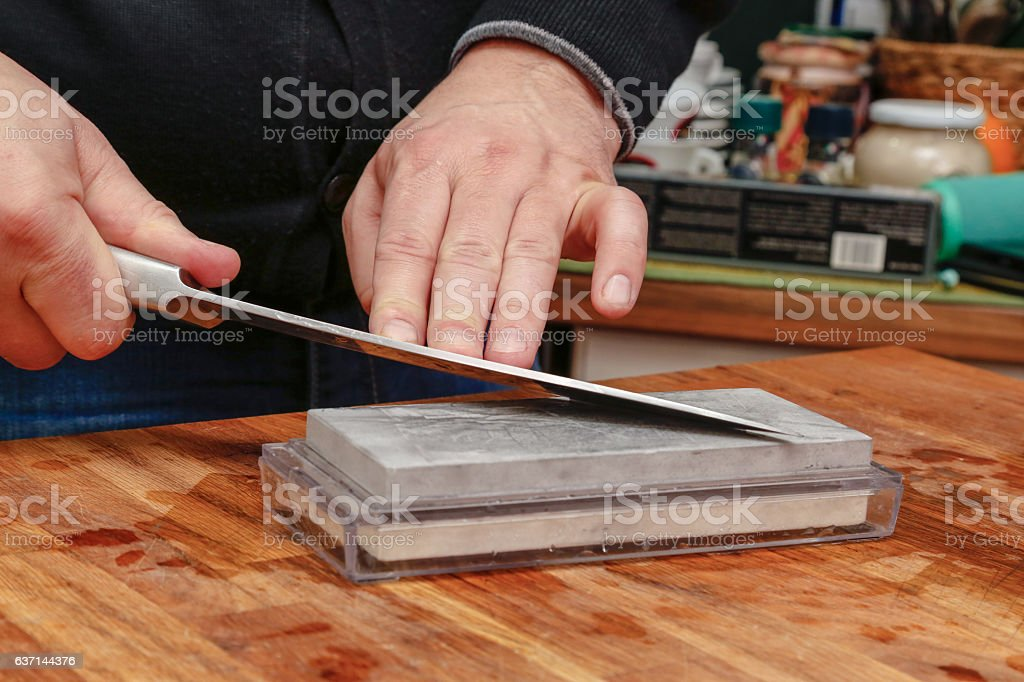 Sharpening knife on whetstone. stock photo
