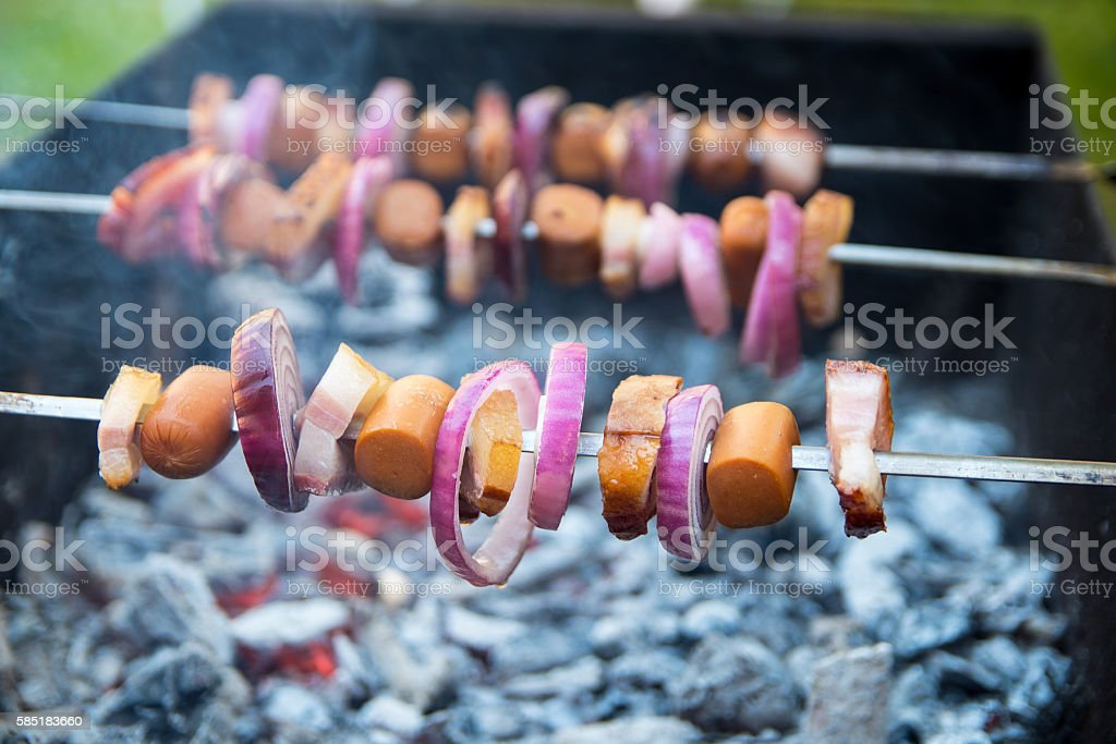 Shashlik with frankfurter, bacon and onion laying on the grill stock photo