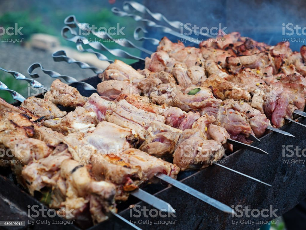 Shashlyk (skewered meat) roasting on charcoals stock photo