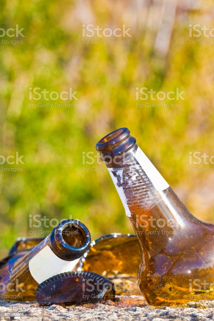 Shattered beer bottle resting on the ground: alcoholism concept stock photo