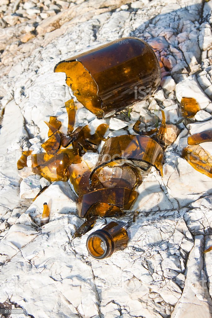 Shattered beer bottle resting on the ground stock photo