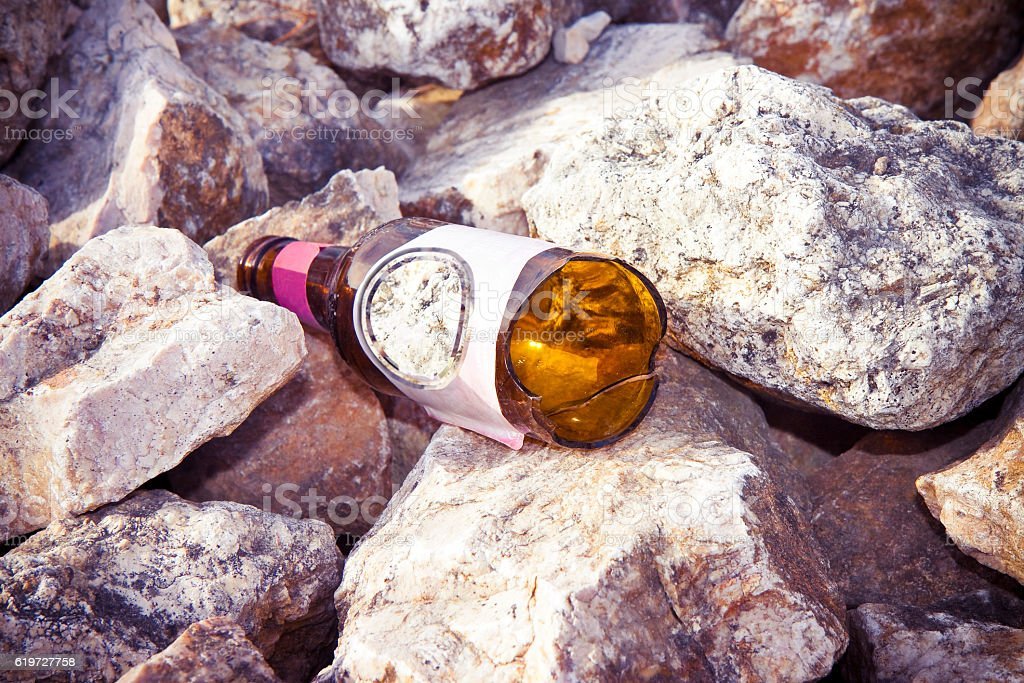 Shattered brown beer bottle resting on the ground stock photo
