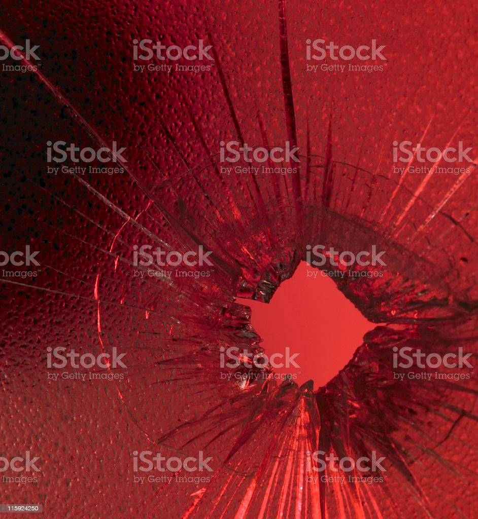 A shattered glass with a bullet hole over a red background stock photo