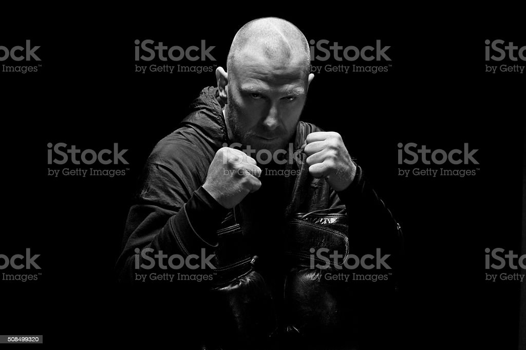 Shaved male fighter posing with boxing gloves and clenched fists stock photo