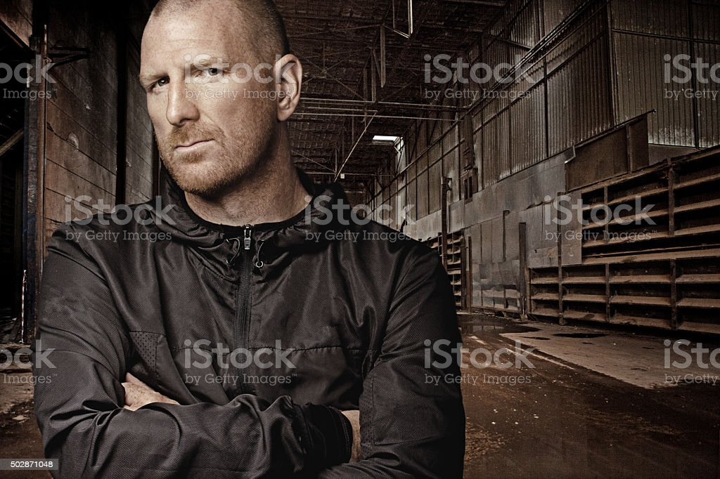 Shaved redhead man posing in urban location stock photo