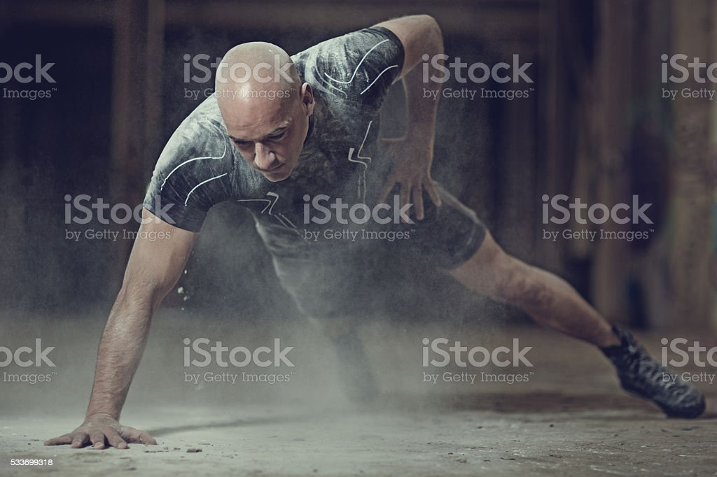 Shaven headed male athlete training in abandoned warehouse stock photo