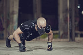Shaven headed male athlete training in warehouse wearing breathing apparatus