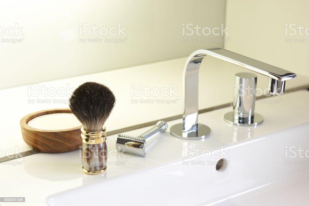 Shaving brush, traditional safety razor, shaving soap, set next to a designer wash basin stock photo