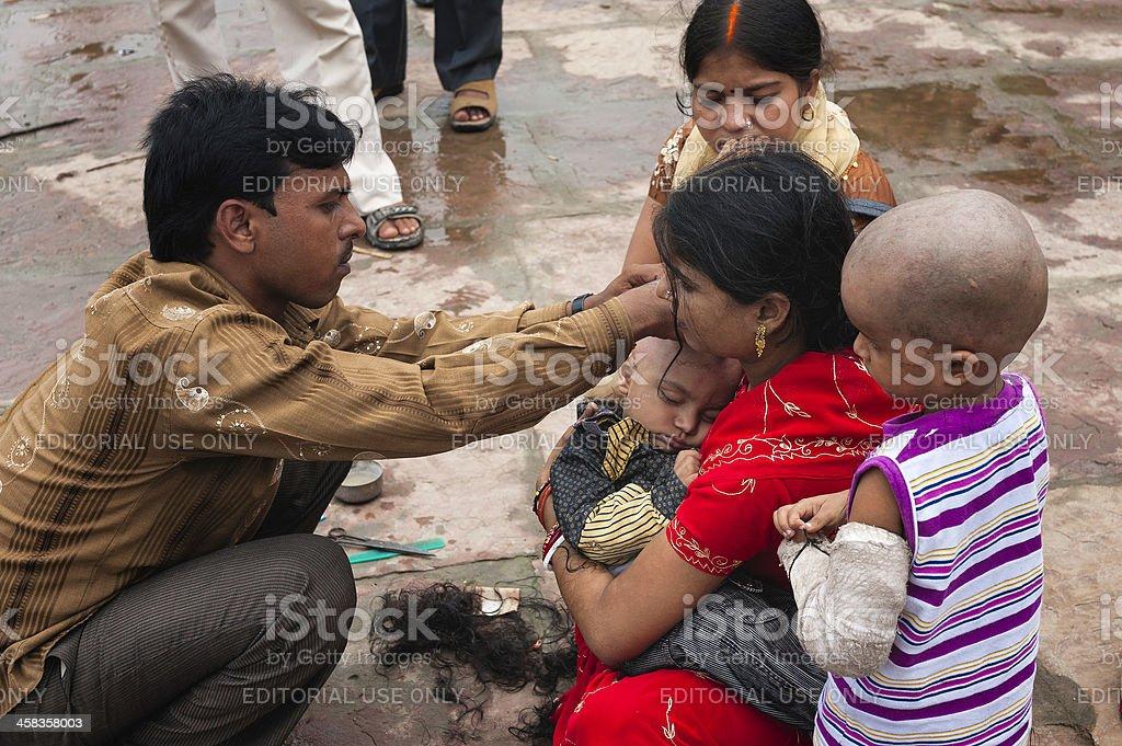 Shaving child's head, rite of passage, Varanasi, India. stock photo