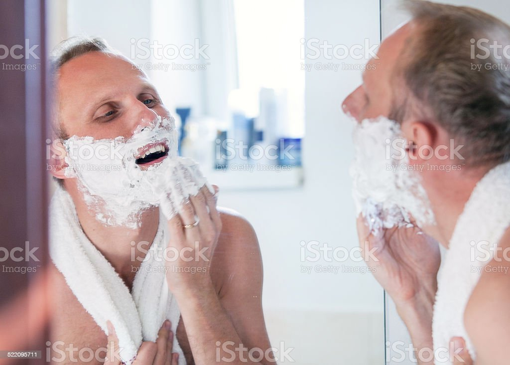 Shaving man near the mirror stock photo