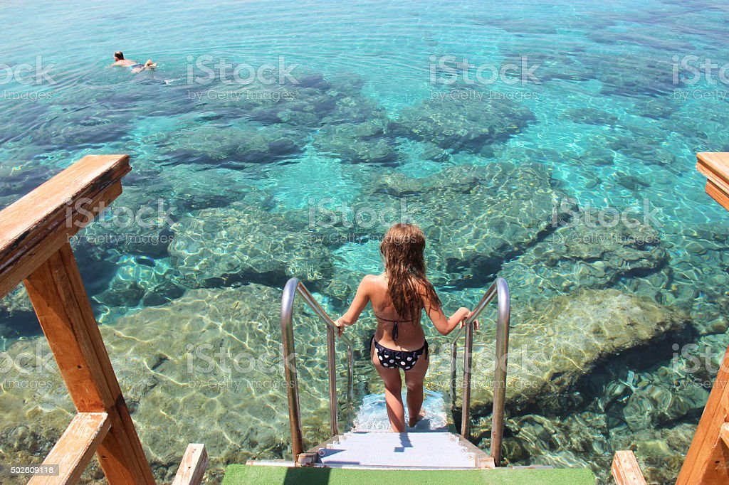 She descends into the clear water of the Mediterranean Sea stock photo