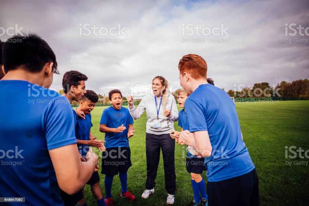 Teenage boys listen to their sports trainer. They gather around...