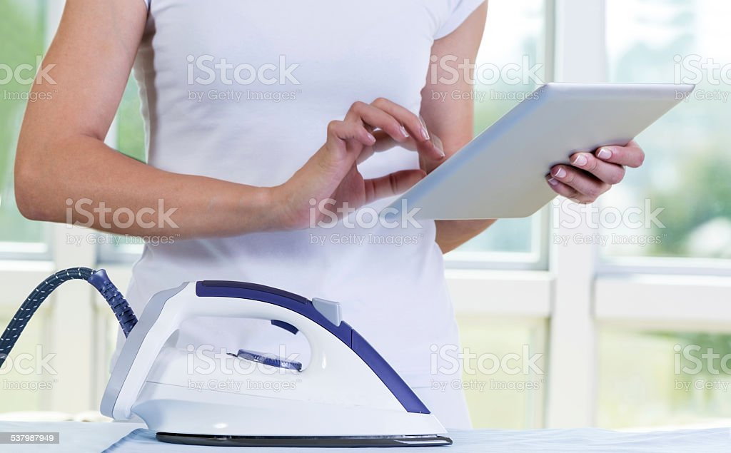 She is  surfing  in digital tablet  while ironing stock photo