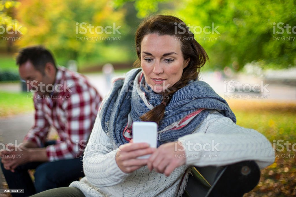 She only has attentions for her smartphone stock photo