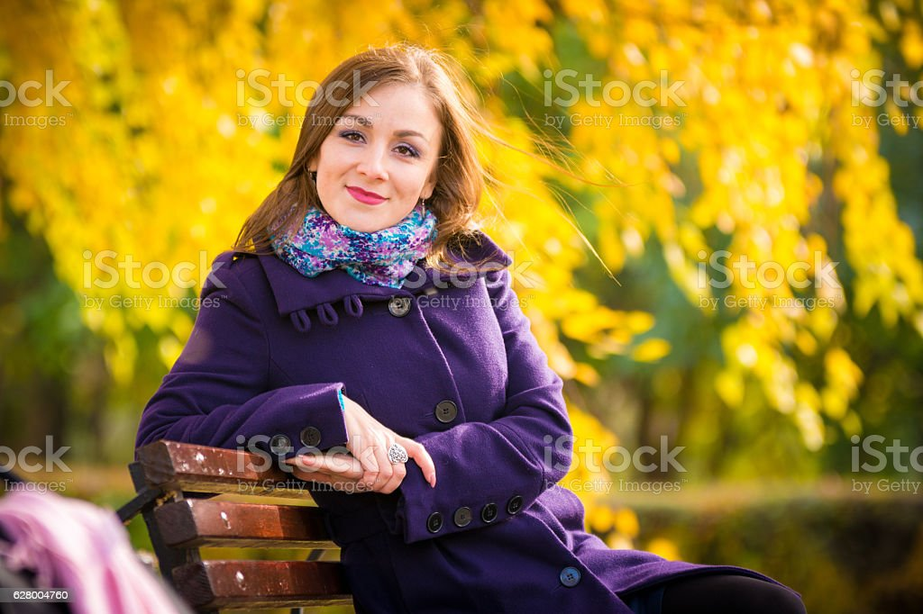 She sat down on the bench and looked at stock photo