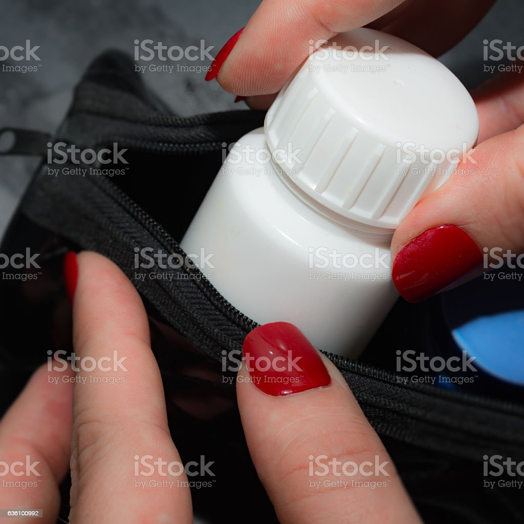 she takes her medicine container  out of her bag stock photo