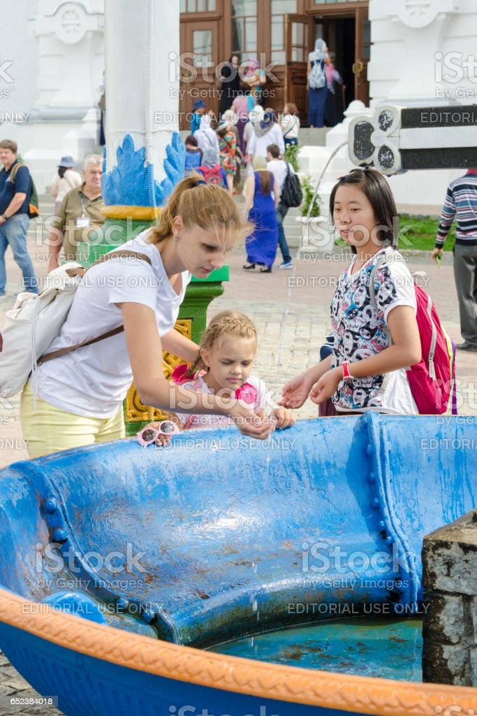 Sergiev Posad - August 10, 2015: She visitor Holy Trinity St. Sergius Lavra washes the baby's face with holy water at the canopy over the cup with a cross stock photo