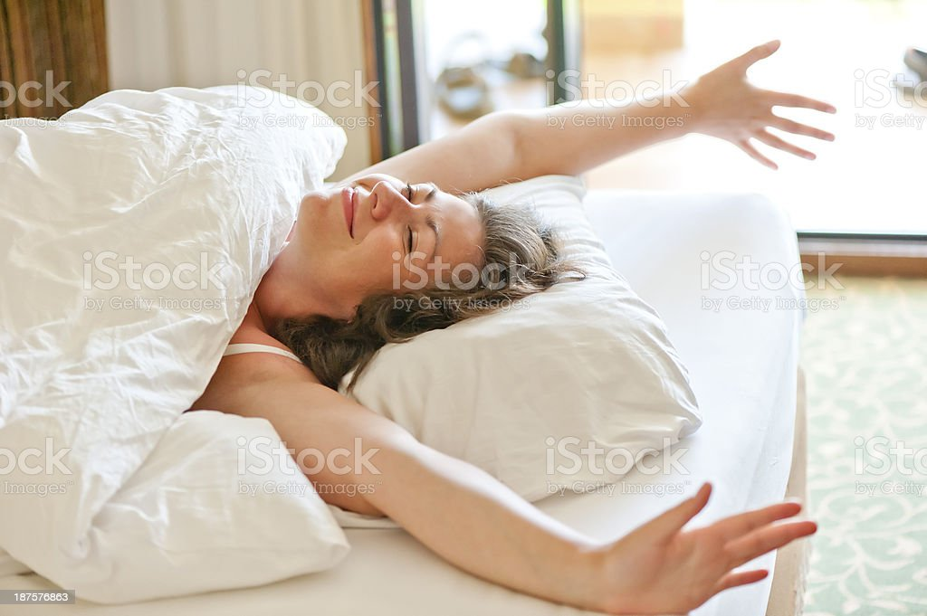 she woke up the morning in bed and stretches stock photo