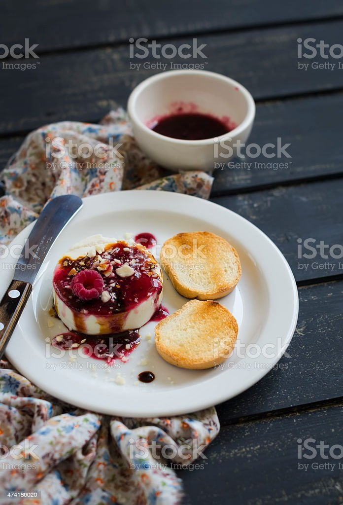 sheep cheese with berry sauce, nuts and balsamic vinegar stock photo