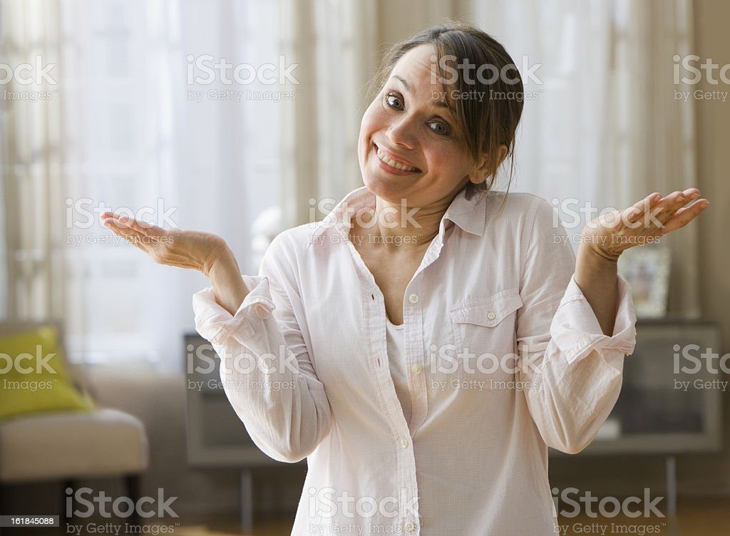 Sheepish woman shrugging with her hands up stock photo