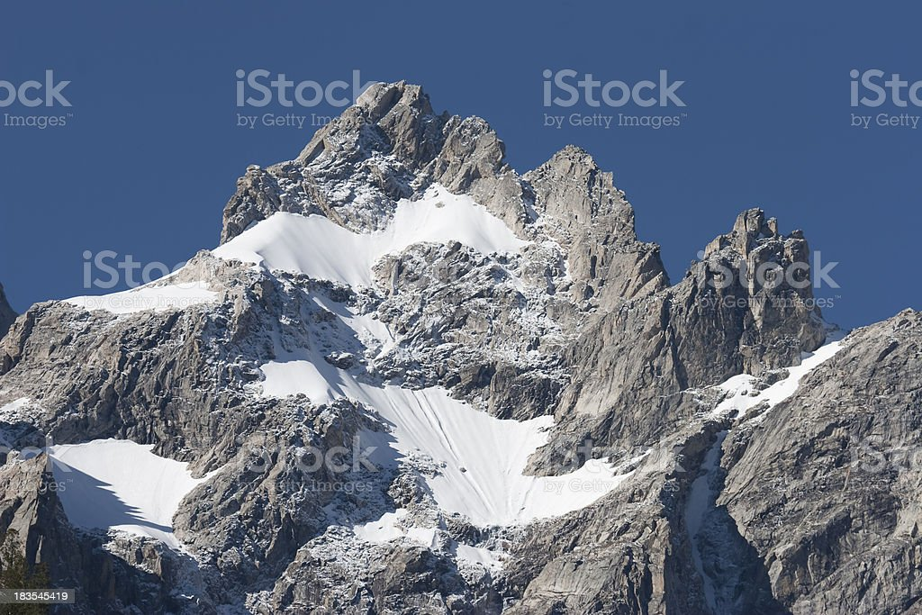 Sheer cliffs and snow fields in Grand Tetons National Park stock photo
