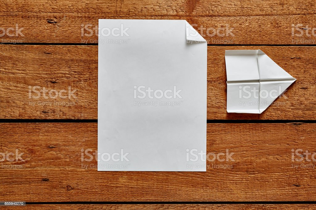 sheet of paper and folded paper plane