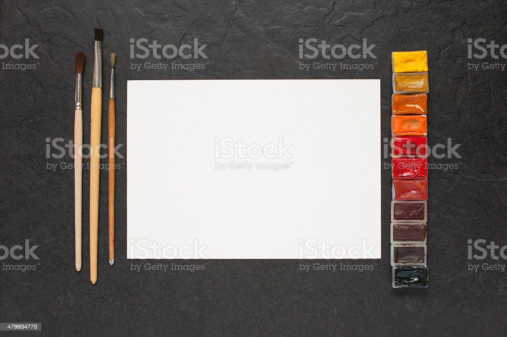 Sheet of paper and water colors on the table stock photo