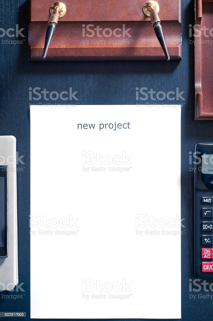 sheet of paper on table with the word new project stock photo
