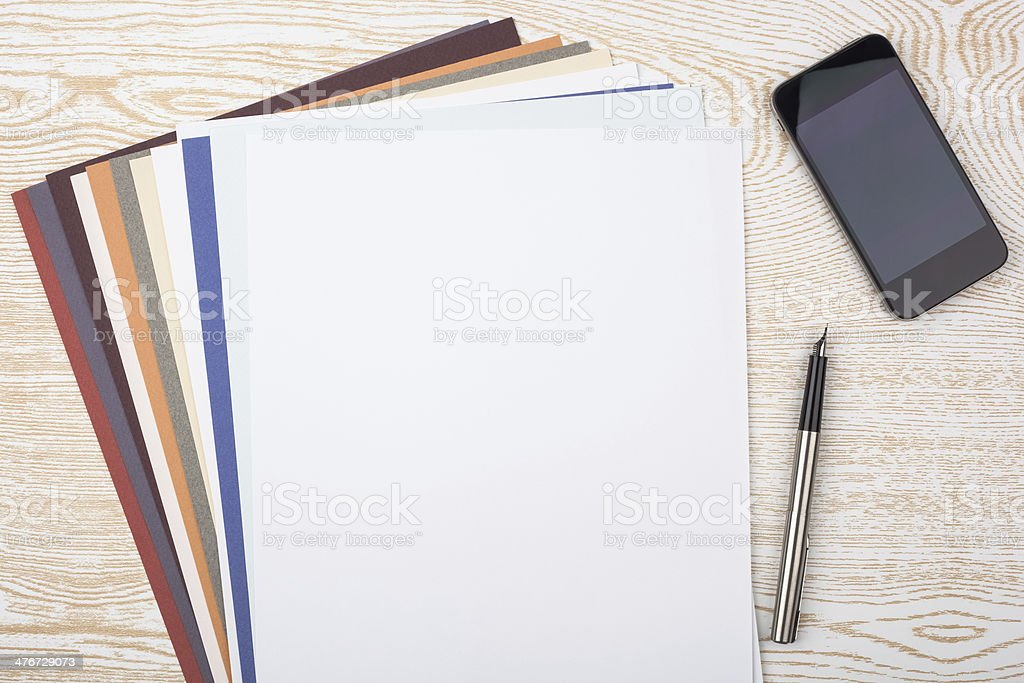 Sheets of multicolored paper on wooden texture royalty-free stock photo