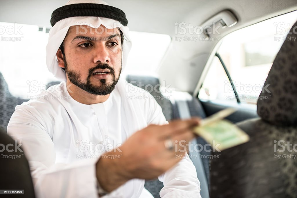 sheik inside a taxi paying the driver stock photo