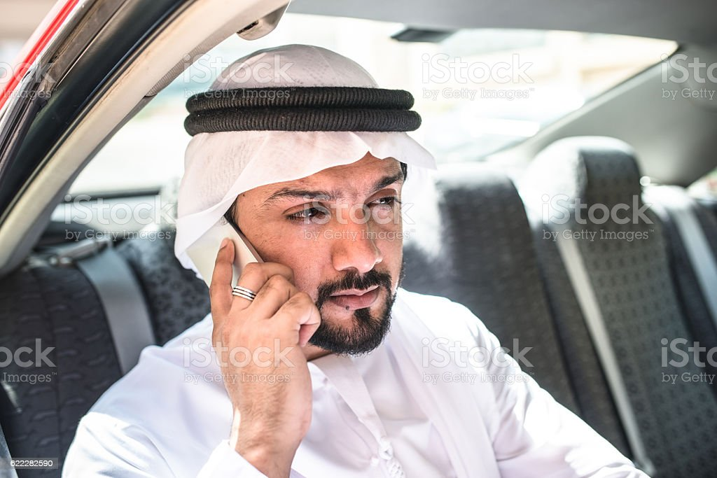 sheik on the phone inside a taxi stock photo