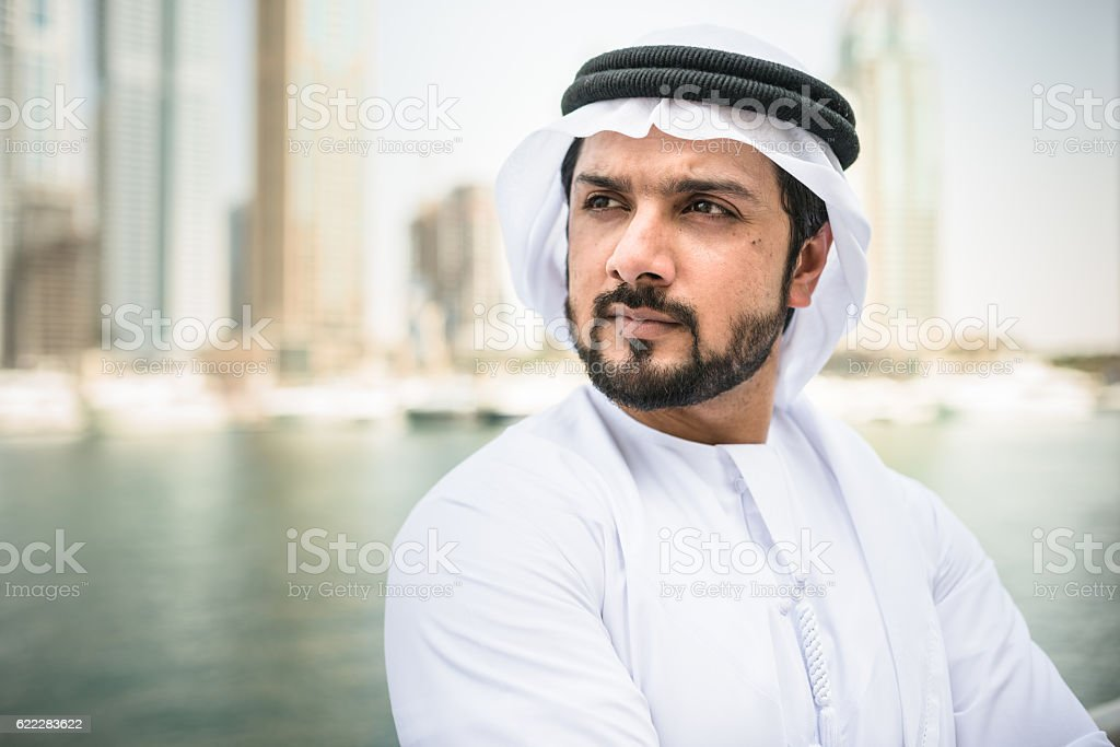 sheik standing pensive on dubai marina stock photo