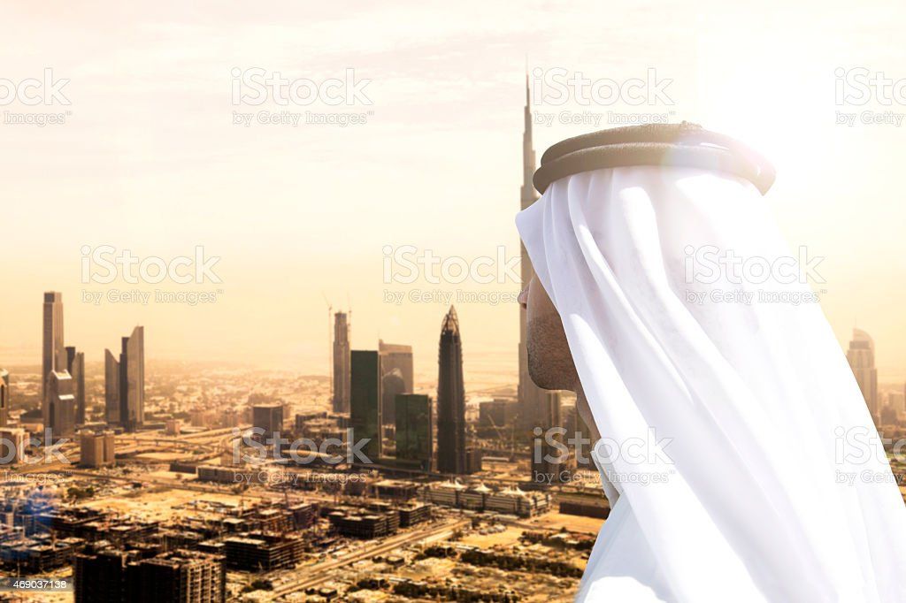 Sheikh looking to Dubai downtown skyscrapers and office buildings stock photo