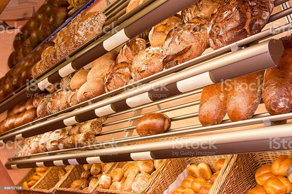 Shelf in a bakery with loaves of bread and rolls stock photo