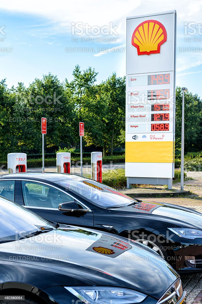 Shell gas station next to a Tesla supercharger charging station stock photo