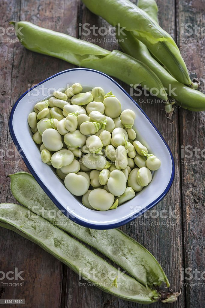Shelled Broad beans in enamelware on wood surface royalty-free stock photo