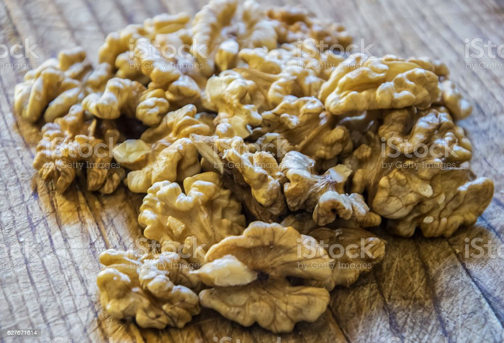 Shelled walnuts on wooden table. stock photo
