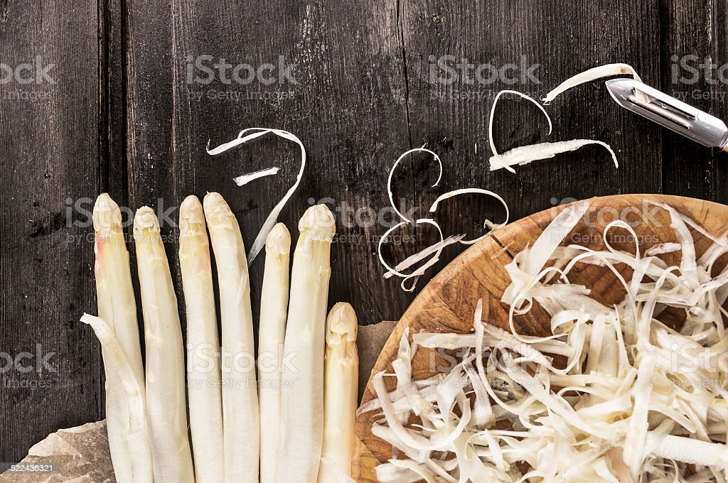 Shelled white asparagus with peelings on dark wooden table stock photo