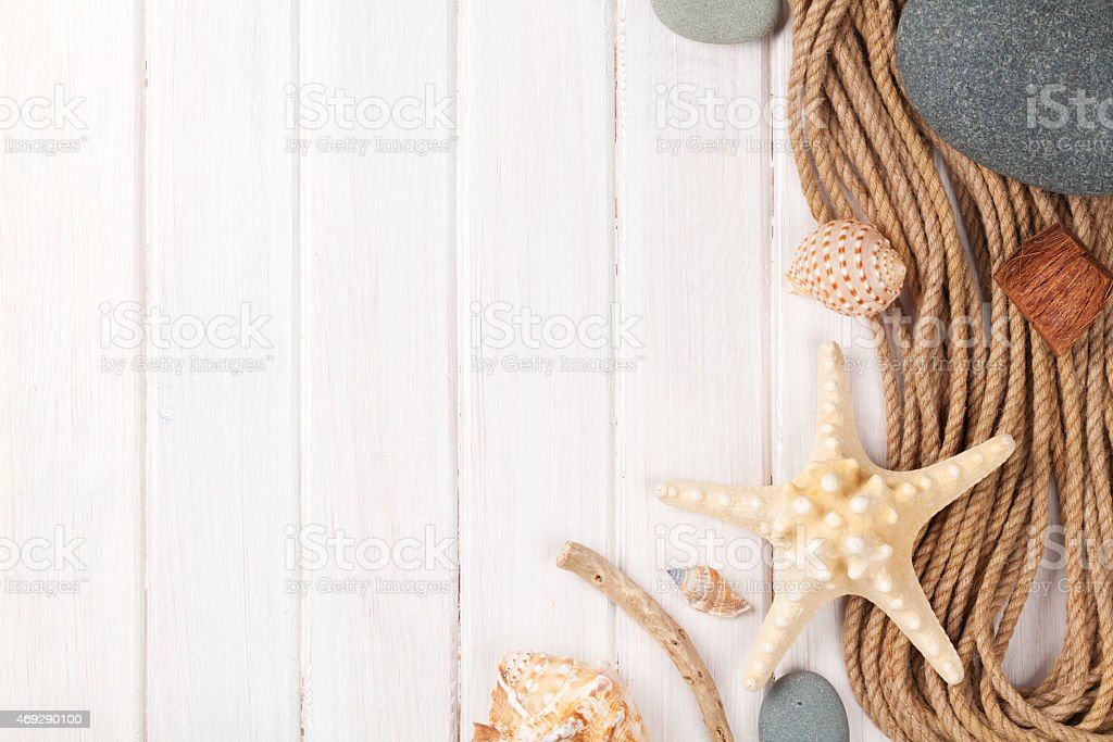 Shells and rope against a white wood fence stock photo