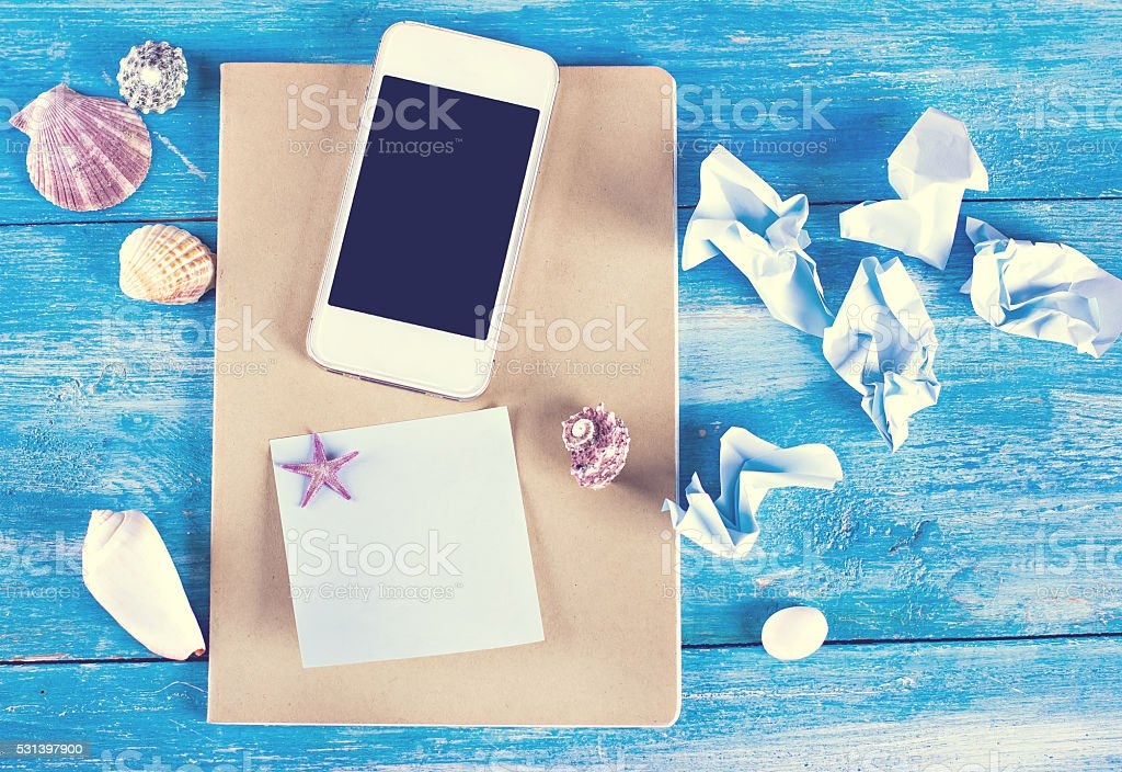 shells, notebook and mobile phone stock photo